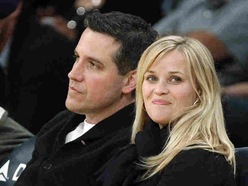 Actress Reese Witherspoon and her husband, Jim Toth, watch an NBA basketball game in Los Angeles in March.