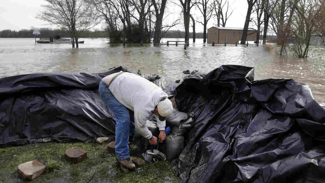 In Clarksville, Mo., Bob Bailey adjusts a pump as he tries to keep floodwater from the Mississippi River out of a rental property Sunday. The small community has worked for days to build a makeshift sandbag levee.