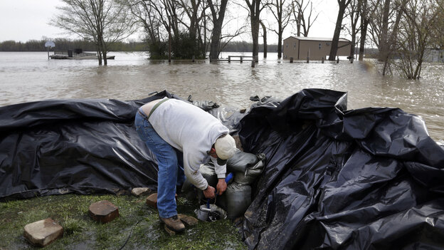 In Clarksville, Mo., Bob Bailey adjusts a pump as he tries to keep floodwater from the Mississippi River out of a rental property Sunday. The small communit