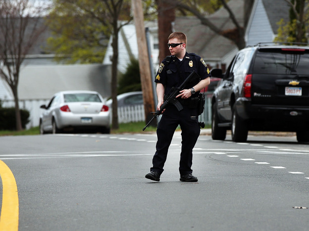 A police officer stands on the street in Watertown, Mass., during the search for bombing suspect Dzhokhar Tsarnaev on Friday.