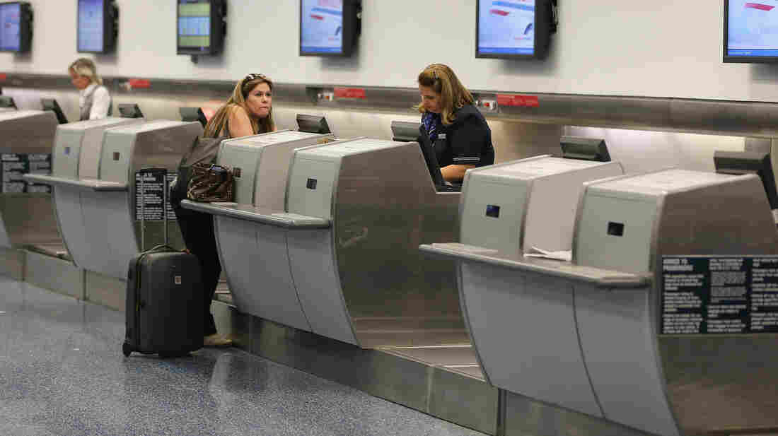 An American Airlines passenger is helped at the ticket counter at Miami International Airport last week. Many airline industry observers expect delays to strike Monday, the first full day of FAA furloughs.