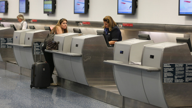An American Airlines passenger is helped at the ticket counter at Miami International Airport last week. Many airline industry observers expect delays to strike Monday, the first full day of FAA furloughs. (Getty Images)