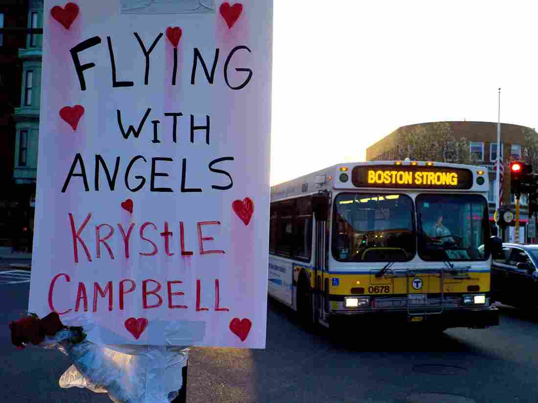 """A sign reading """"Flying With Angels Krystle Campbell,"""" is seen Monday as a passing MBTA bus with """"Boston Strong"""" displayed on its message board drives through Medford, Mass. A funeral service for Campbell, one of the three people killed in the marathon bombings, was held later in the day."""