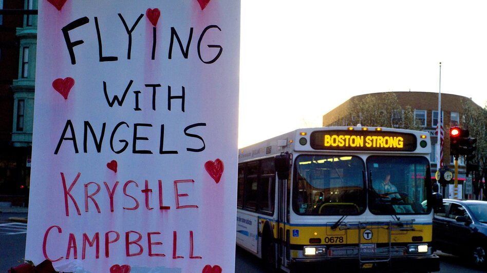 "A sign reading ""Flying With Angels Krystle Campbell,"" is seen Monday as a passing MBTA bus with ""Boston Strong"" displayed on its message board drives through Medford, Mass. A funeral service for Campbell, one of the three people killed in the marathon bombings, was held later in the day. (EPA /LANDOV)"
