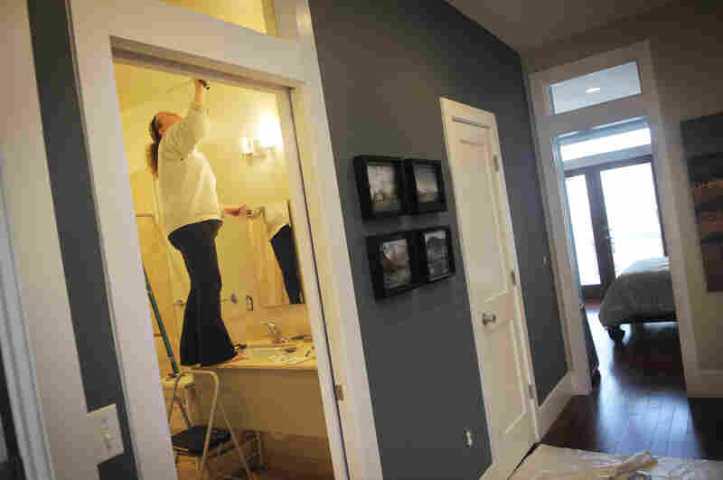 Amanda Cowley repaints her bathroom during renovations made to her new three-bedroom, two-bathroom townhouse.