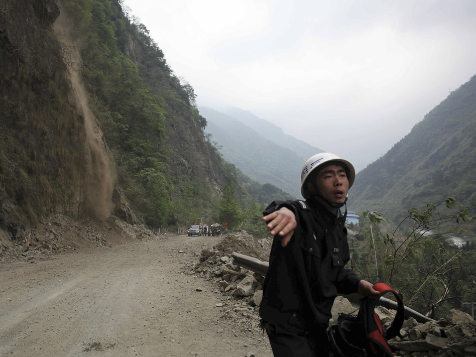 As rocks and dirt tumble down a mountainside (at left), a police officer urges people to stay back on a road in  Baoxing county, Sichuan province, on Monday. Rescuers are having a hard time getting to victims of Saturday's strong earthquake because of aftershocks and landslides.