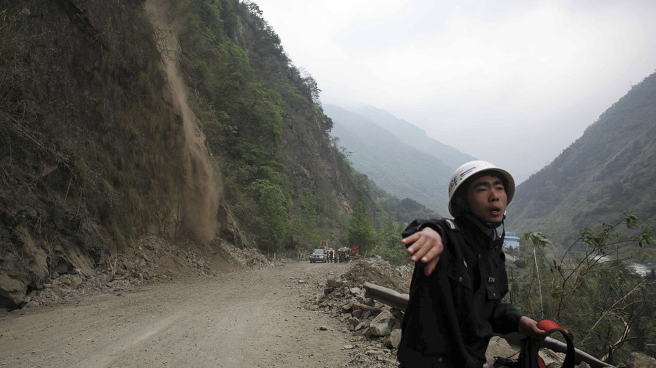 As rocks and dirt tumble down a mountainside (at left), a police officer urges people to stay back on a road in  Baoxing county, Sichuan province, on Monday. Rescuers are having a hard time getting to victims of Saturday's strong earthquake because of aftershocks and landslides. (Reuters /Landov)