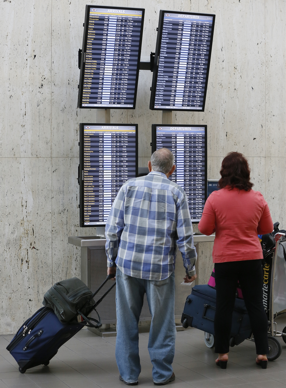 Passengers check their flight status at Los Angeles International airport on Monday. The FAA said staffing cuts were causing delays in the Eastern U.S.