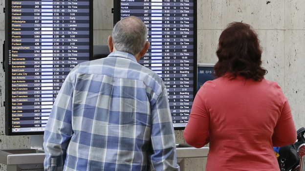 Passengers check their flight status at Los Angeles International airport on Monday. The FAA said staffing cuts were causing delays in the Eastern U.S. (AP)