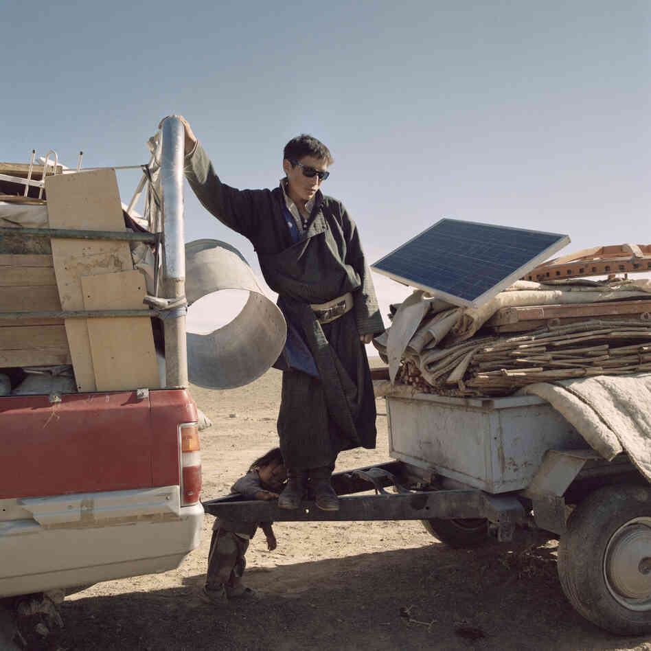 A nomad family loads their tent and belongings onto a jeep as it is about to leave. Mongolia, Gobi, Omongovi, 2012.