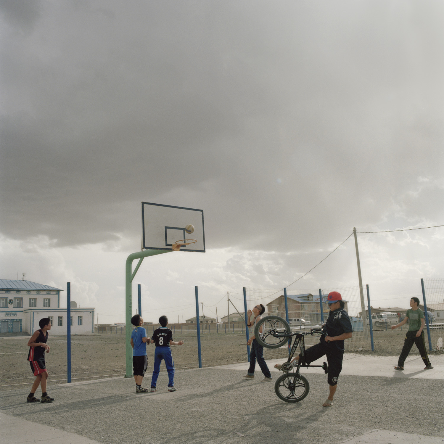 Young boys play in the only public place in the village -- the basketball field of the public school. Mongolia, Gobi, Tsogttsestii sum, 2012.