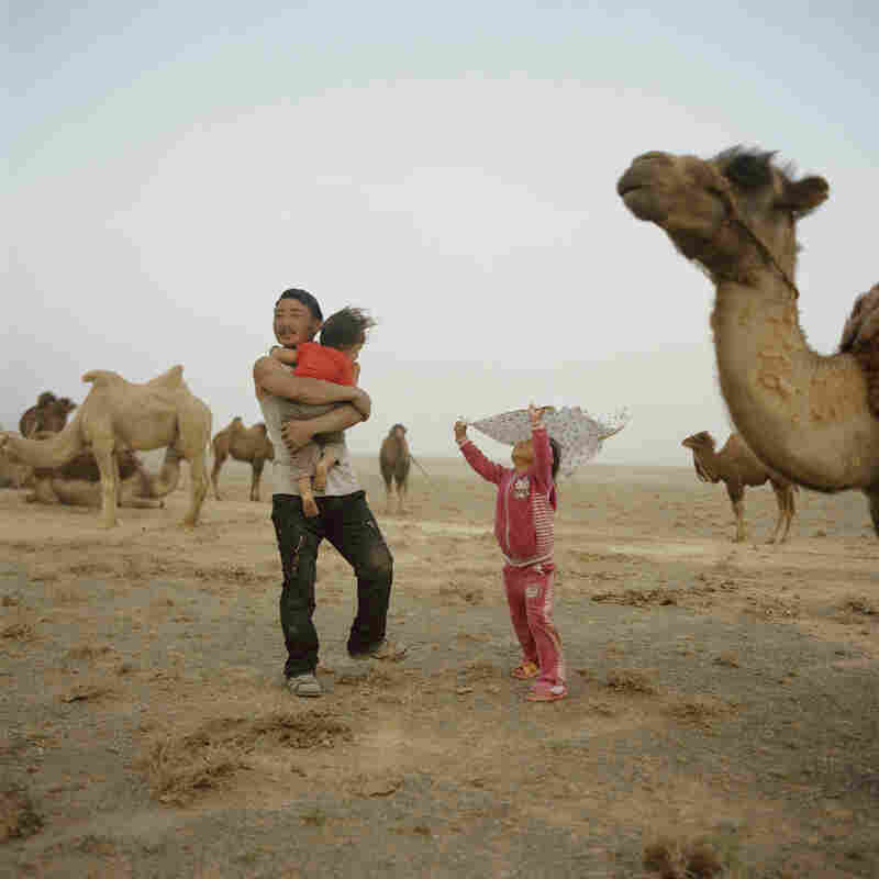 Tuvshinbayar with his children during a sandstorm. Mongolia, Gobi, Omongovi, 2012.