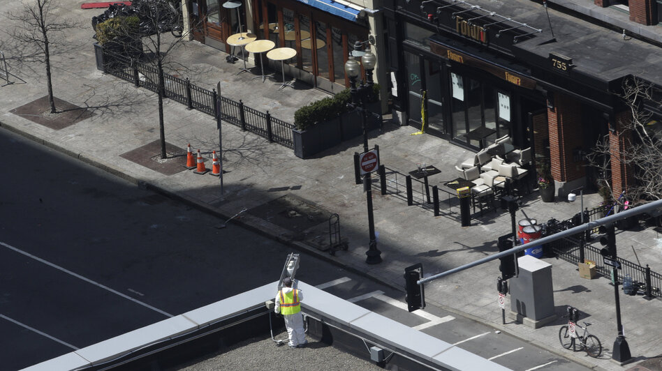 An investigator inspects the area near a surveillance camera on the roof of the Lord & Taylor store near the Boston Marathon finish line on Thursday. That camera provided the first glimpse of the men who allegedly planted the bombs.