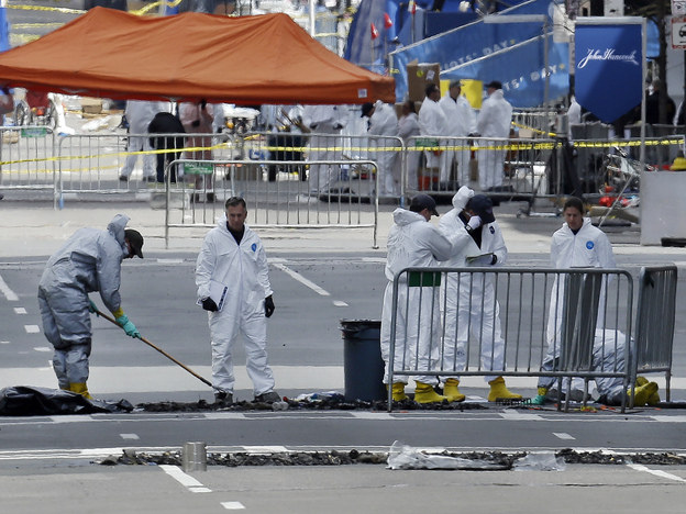Investigators in protective suits examine material on Boylston Street in Boston on April 18, three days after the deadly bombings. The explosive devices were relatively simple to make and law enforcement officials come across them on a regular basis, officials say.