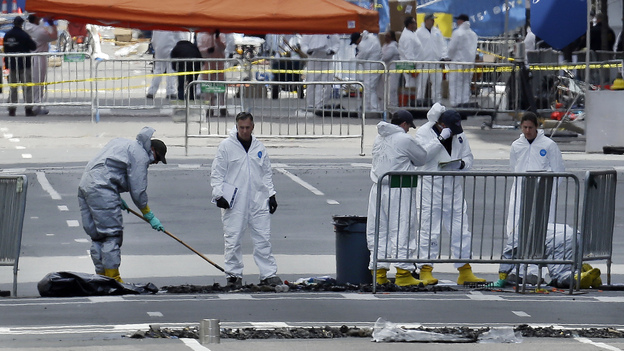 Investigators in protective suits examine material on Boylston Street in Boston on April 18, three days after the deadly bombings. The explosive devices were relatively simple to make and law enforcement officials come across them on a regular basis, officials say. (AP)