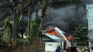 Firefighters try to extinguish a fire during the riots in Meiktila in March. More than 40 people died during three days of violence in the town.