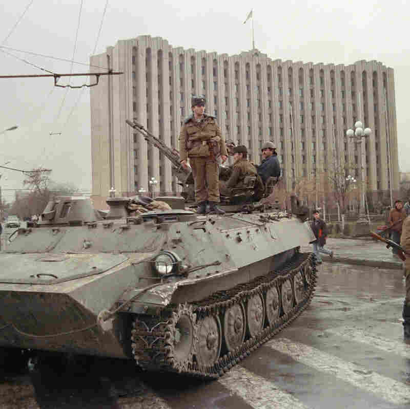 A Chechen separatist soldier stands on an APC, guarding the presidential palace on Grozny's central square, on November 25, 1994. Tension is rising in Grozny following a buildup of Russian troops along the border with the breakaway Chechen republic. (Photo credit should read IVAN SHLAMOV/AFP/Getty Images)