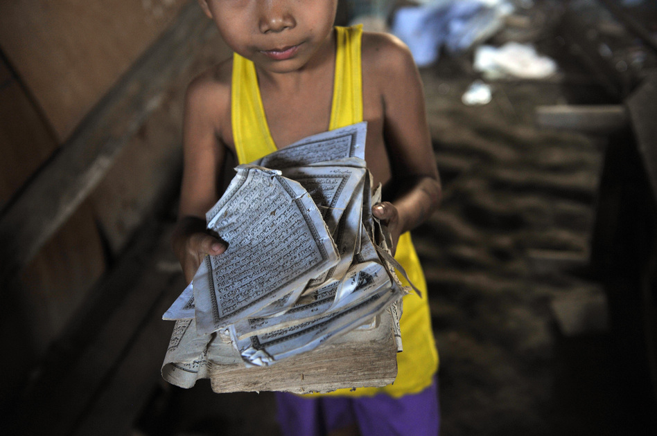 A boy shows the torn pages of a Quran at his home after sectarian violence spread through Zeegone, about 90 miles north of Yangon, in late March. More than 100 people were killed in similar incidents in the country's west last year. (AFP/Getty Images)