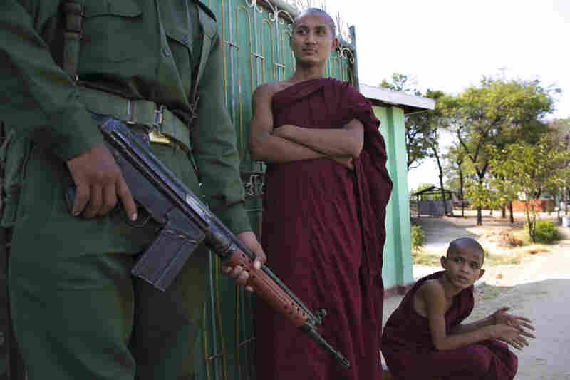 Men wait by an officer near their destroyed home. U Win Htein, who represents Meiktila in Parliament, says armed mobs initially prevented police and firefighters from approaching burning buildings. The crowds let them pass, he says, only after Buddhist monks climbed onto the fire engines.