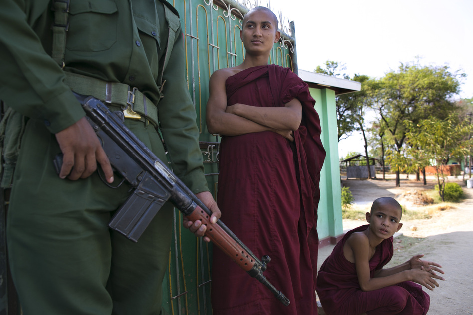 Men wait by an officer near their destroyed home. U Win Htein, who represents Meiktila in Parliament, says armed mobs initially prevented police and firefighters from approaching burning buildings. The crowds let them pass, he says, only after Buddhist monks climbed onto the fire engines.  (Getty Images)