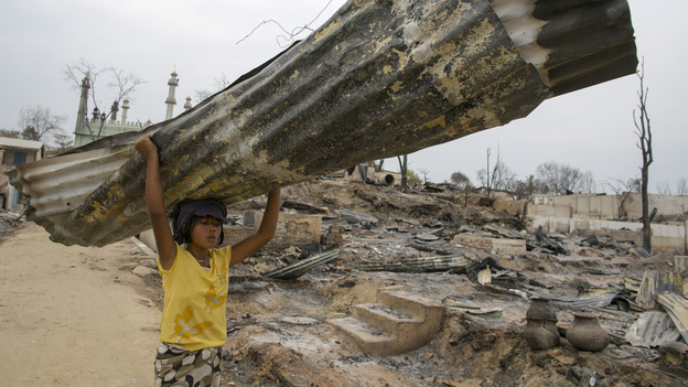 A Myanmarese girl carries away a tin roof in Meiktila, Myanmar. Violence between Buddhists and Muslims in March destroyed large areas of the town and left thousands of Muslims homeless. (Getty Images)