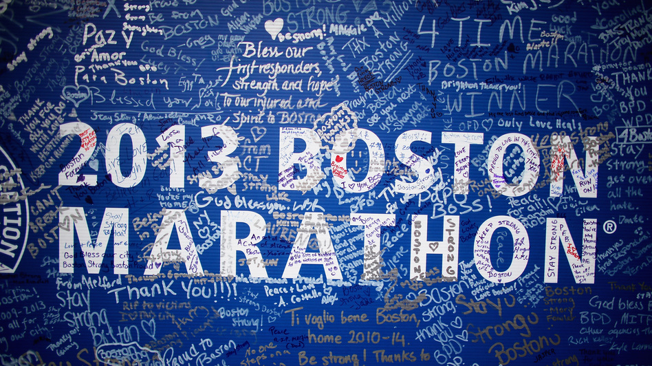 Signatures and messages adorn a Boston Marathon poster on Tuesday near the site of the April 15 bombings. (Mario Tama/Getty Images)