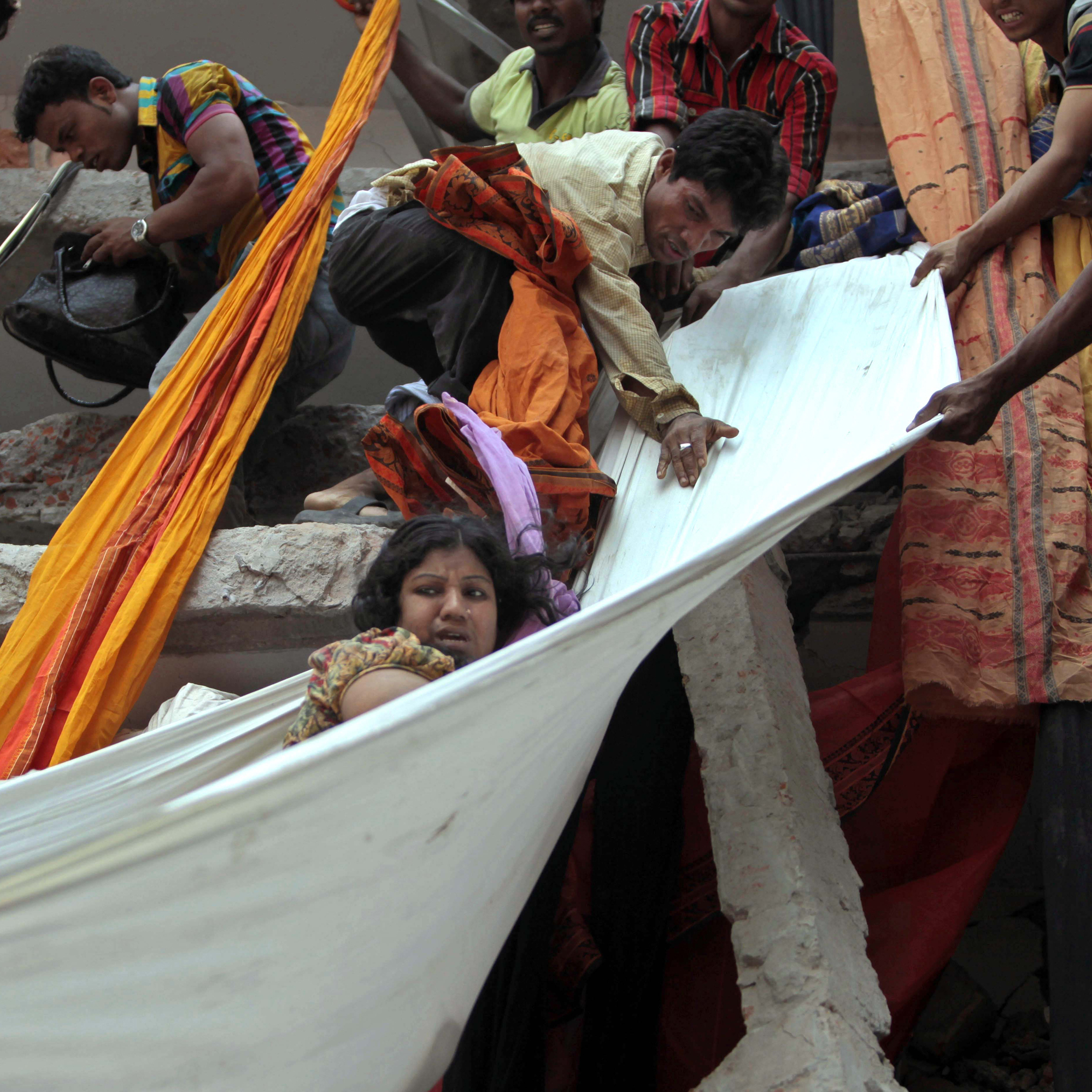 Rescue workers use pieces of clothes to bring down a survivor after an eight-story building housing several garment factories collapsed Wednesday in Savar, near Dhaka, Bangladesh.