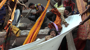 Rescue workers use pieces of clothes to bring down a survivor after building collapsed in Savar, near the capital, Dhaka.