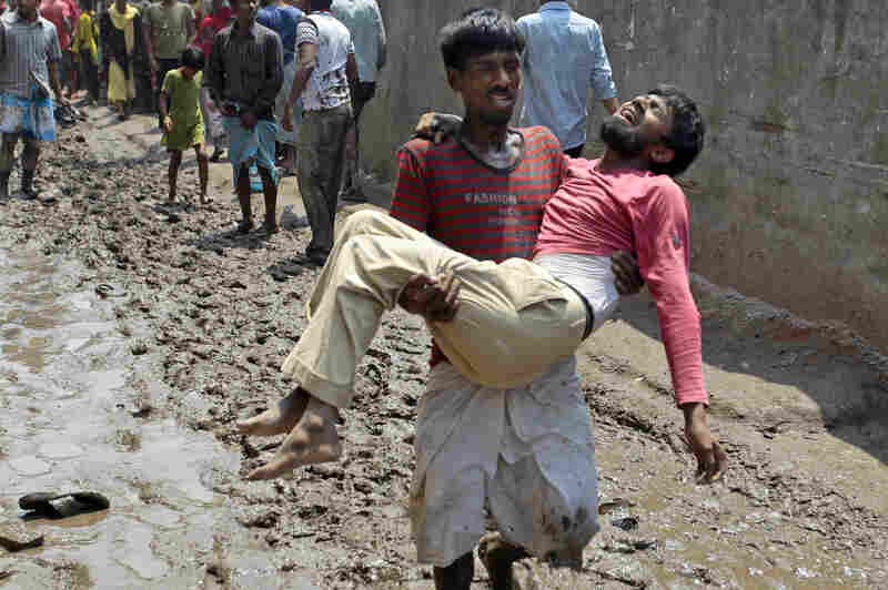 A survivor reacts in pain as he is carried by a rescuer.