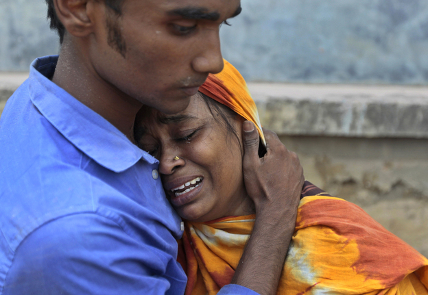 Relatives mourn a victim at the site of the building collapse. (AP)