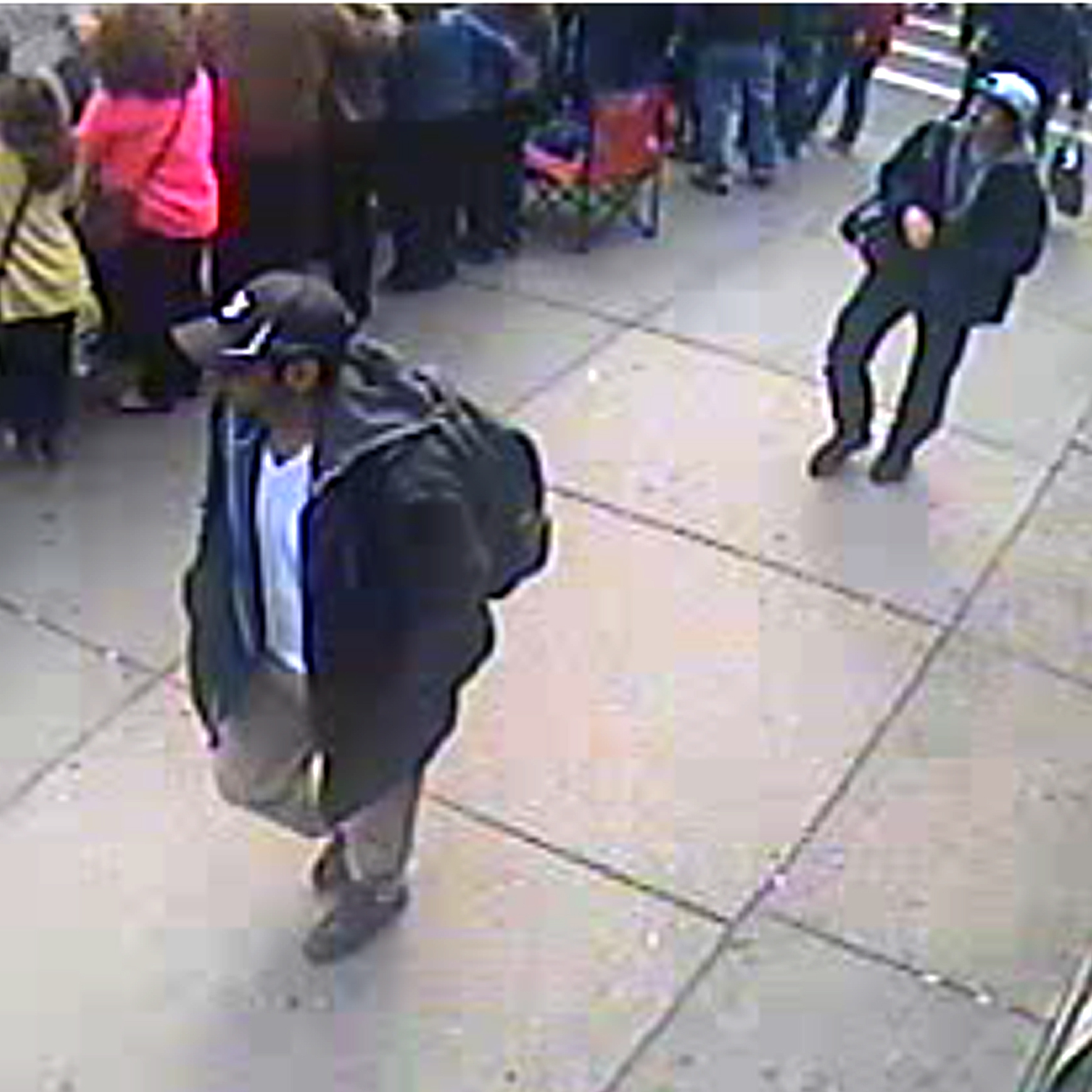 Surveillance video released by the FBI showed two young men, who authorities later identified as Tamerlan Tsarnaev (in black cap) and his brother, Dzhokhar (in white cap), at the scene shortly before the Boston Marathon bombings.