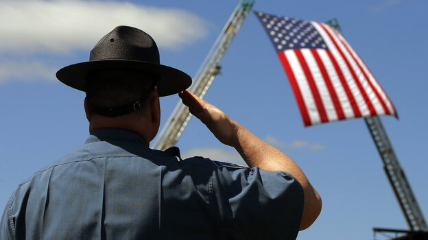 A Massachusetts state trooper salutes Wednesday during the memorial service for Massachusetts Institute of Technology (MIT) police officer Sean Collier on the school's campus in Cambridge, Mass.
