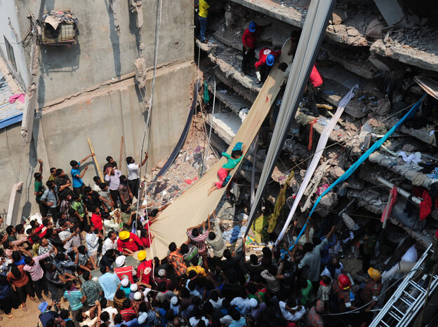 Volunteers use a length of textile as a slide to move victims Thursday from the rubble of a collapsed building in Savar, Bangladesh.