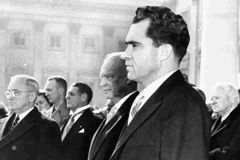 "Vice President Nixon, foreground, President Eisenhower, immediately behind, former President Truman, left, and former President Hoover, right, stand on the inauguration stand in front of the Capitol, January 20, 1953, during the singing of ""The Star Spangled Banner"" at Eisenhower's swearing-in ceremony."