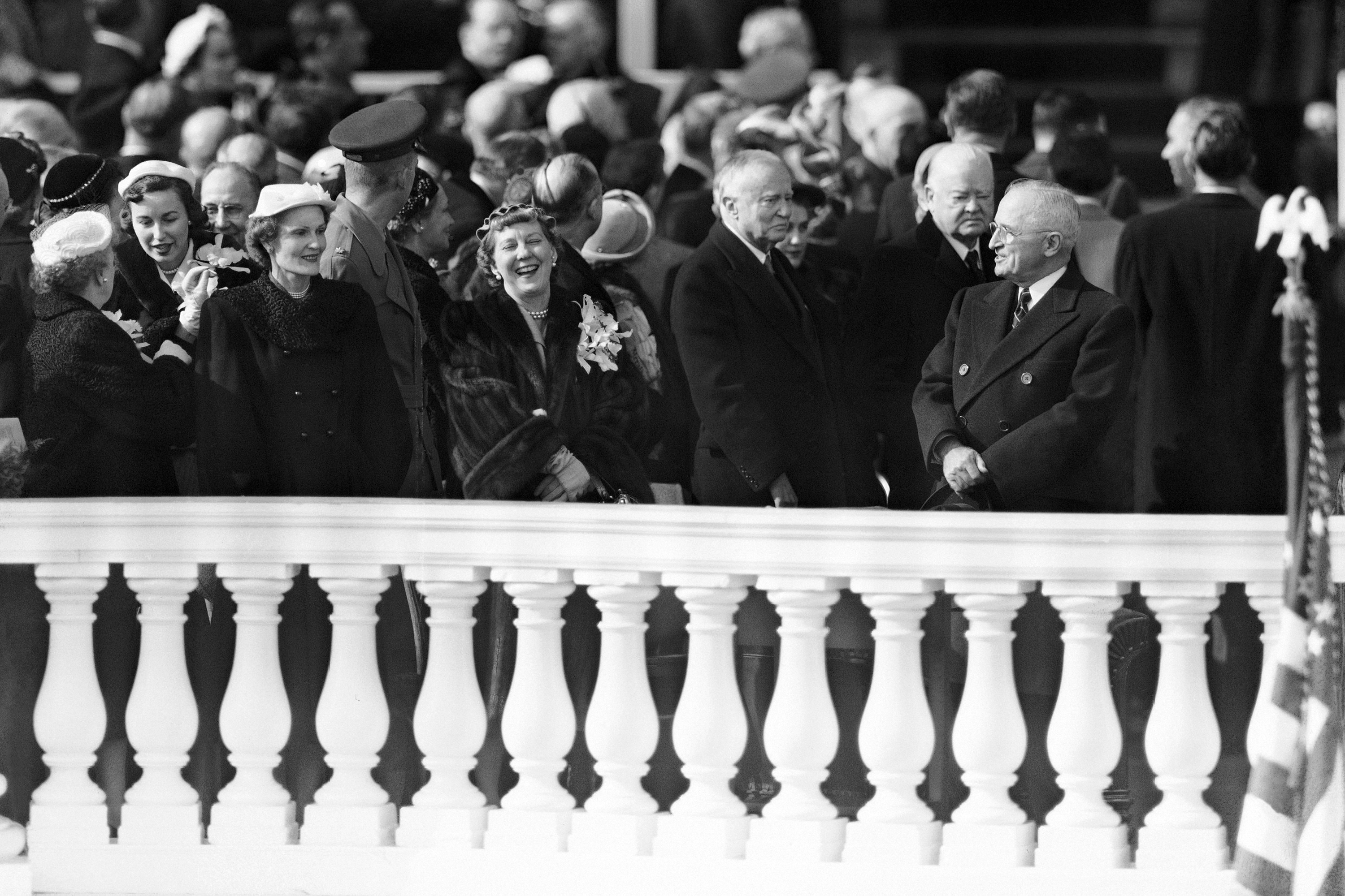 Outgoing President Harry Truman, at right, and new first lady Mamie Eisenhower, left, appear to be sharing a joke on presidential inauguration stand in Washington, Jan. 20, 1953, but ex-president Herbert Hoover, behind Truman, takes a serious view of the situation.