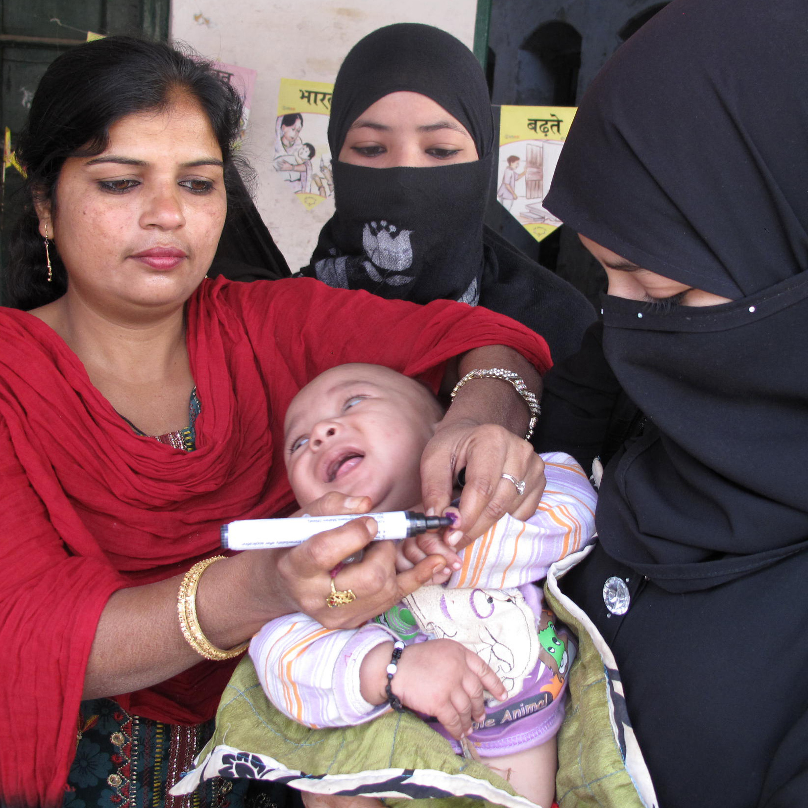 A health worker marks a baby's finger after giving her a polio vaccine in Moradabad, India.