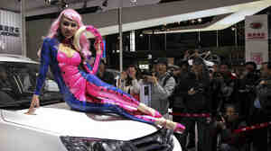 Models abound at this week's Shanghai auto show. This one, in a latex cat suit, was drawing attention to an SUV by Landwind, a Chinese company that sells about 10,000 vehicles a year.