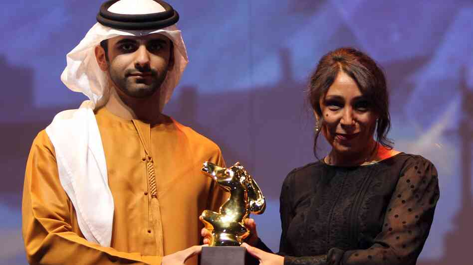 Saudi Arabia film director Haifaa Al-Mansour (right) receives the award of best film for her movie Wadjda at Dubai International Film Festival in Dubai, United Arab Emirates, on Dec. 16, 2012.