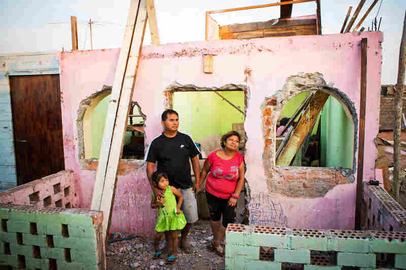 The community of El Ayllu in Lima, Peru, has been demolished to make way for an airport expansion. Residents received money to relocate, but their historic sense of community cannot be rebuilt. Here, Ricardo Galvez, Giovanna Meneses Pisco and Arely Betzabe stand in front of their former home in El Ayllu. The family was back in the neighborhood to gather some of their belongings.