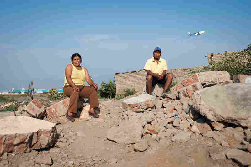 Catalina Guzman Harrimache and her husband, Teofilo Huaman Loayza, sit on the remnants of a home. The home had its own groundwater supply that residents now frequent to wash clothes while sitting amid the rubble. In the background, the main terminal of Jorge Chavez International Airport can be seen.