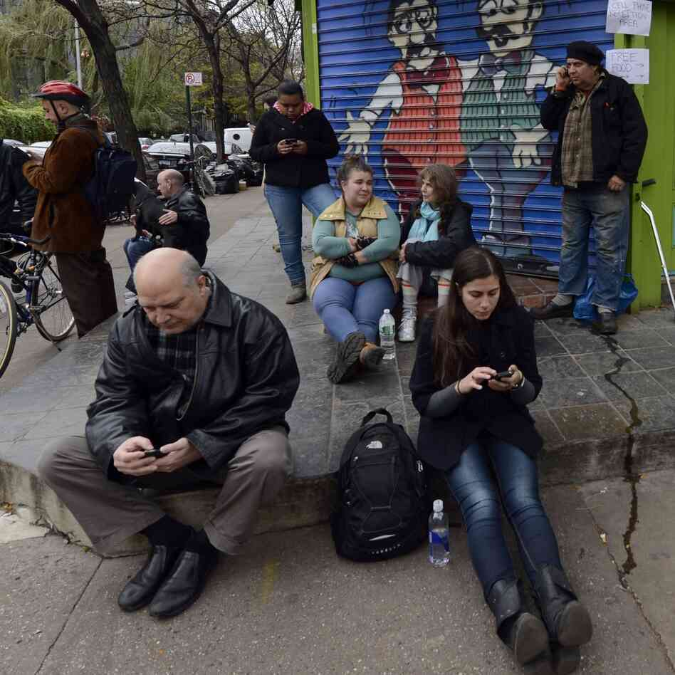 Residents of the East Village in New York City look for cellphone reception Nov. 1 after Hurricane Sandy