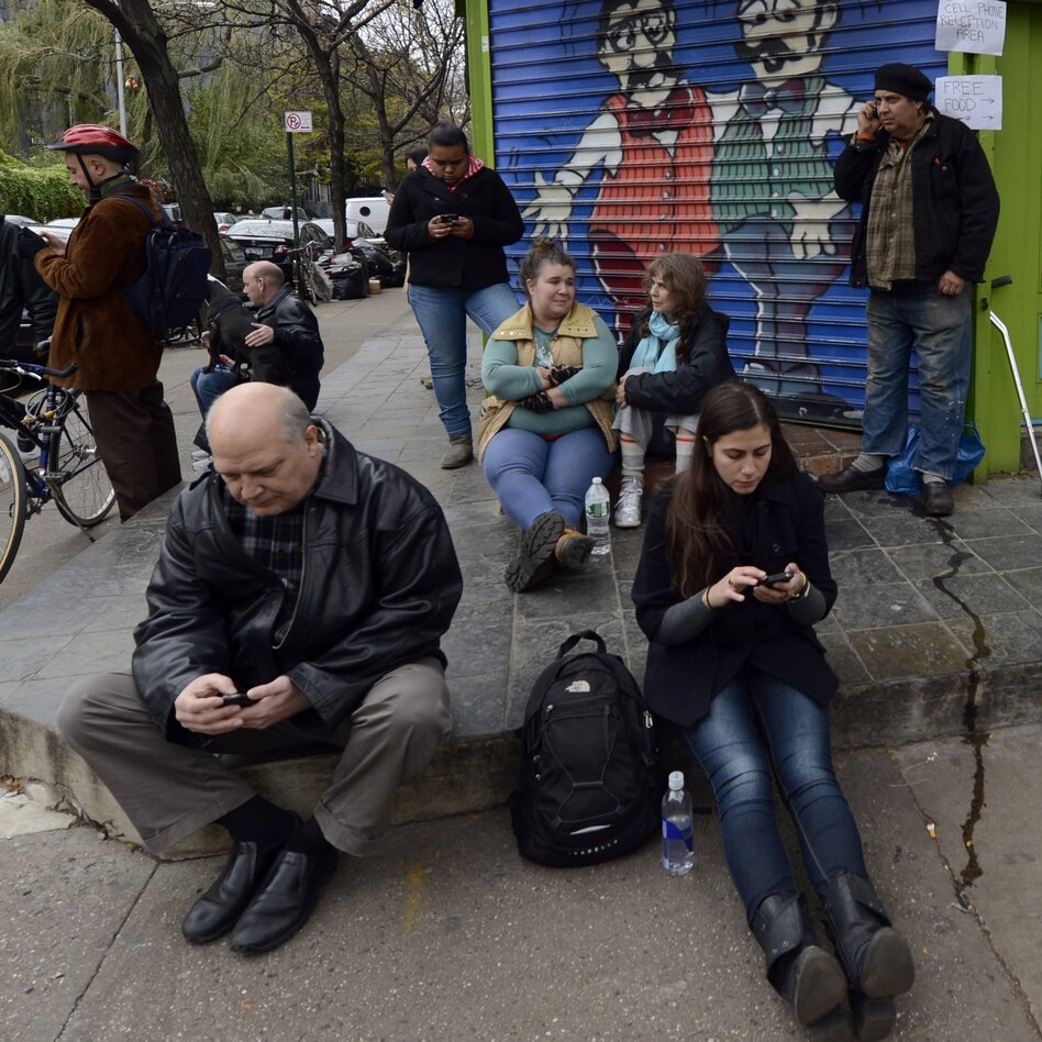 Residents of the East Village in New York City look for cellphone reception Nov. 1 after Hurricane Sandy wiped out power and some cell towers. (Timothy A. Clary/AFP/Getty Images)