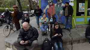Residents of the East Village in New York City look for cellphone recepti