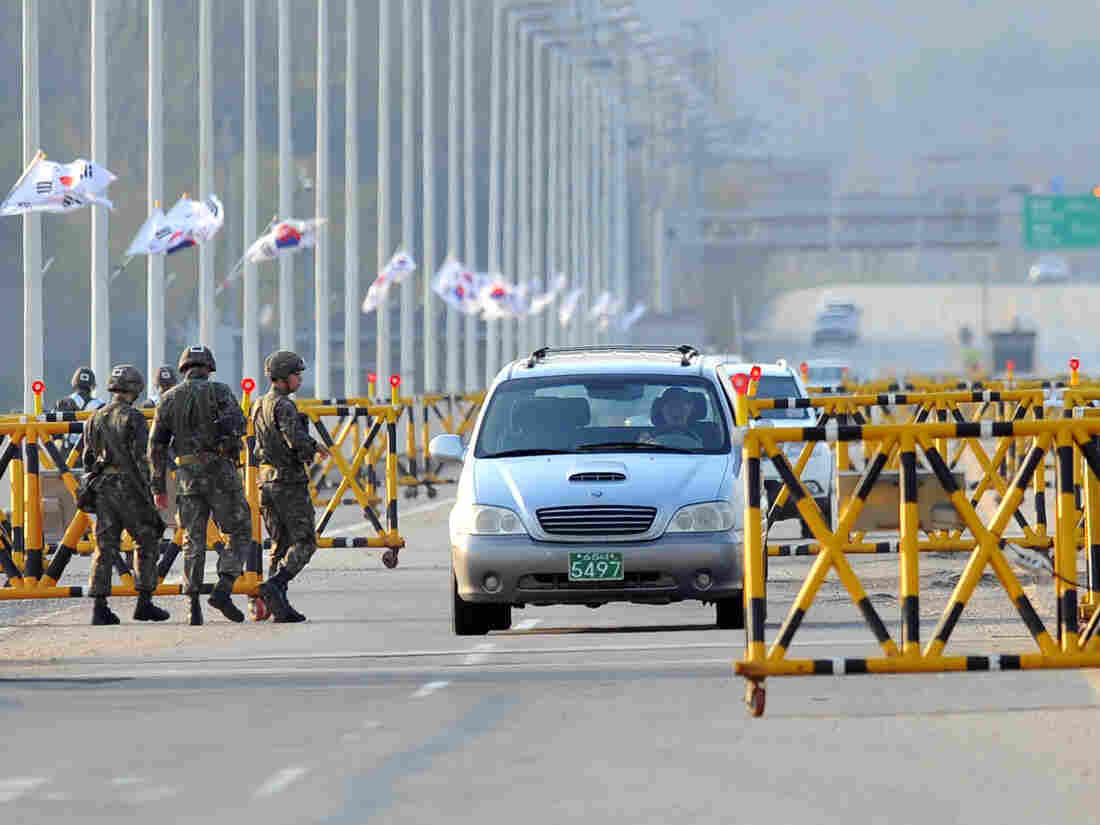 South Korean soldiers stand beside barricades as cars drive on the road leading to North Korea's Kaesong industrial complex on Friday.