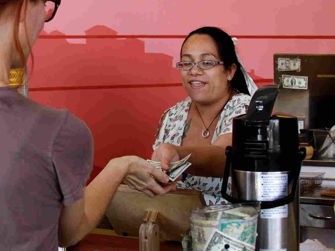 Carmen Castillo, an employee of Café de Leche, gives change back to a customer.