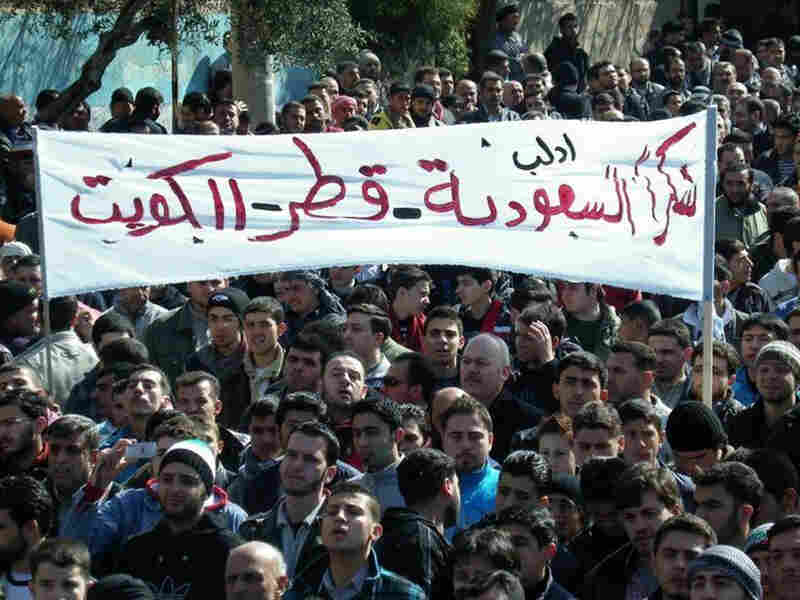 "Anti-Syrian regime protesters hold up a banner in Arabic reading, ""Thank you Saudi Arabia, Qatar and Kuwait,"" during a demonstration in Idlib province, northern Syria, in this March 2, 2012, file photo provided by Local Coordination Committees in Syria."