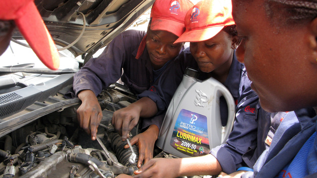 Students at the Lady Mechanic Initiative in Lagos, Nigeria, work on cars in their open air workshop. (NPR)