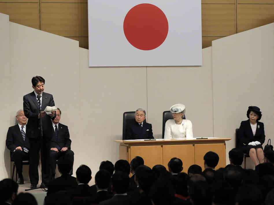Japanese Prime Minister Shinzo Abe delivers a speech Sunday in Tokyo as Emperor Akihito, third from right, and Empress Michiko, second from right, listen during a ceremony marking the day Japan recovered its sovereignty under the San Francis