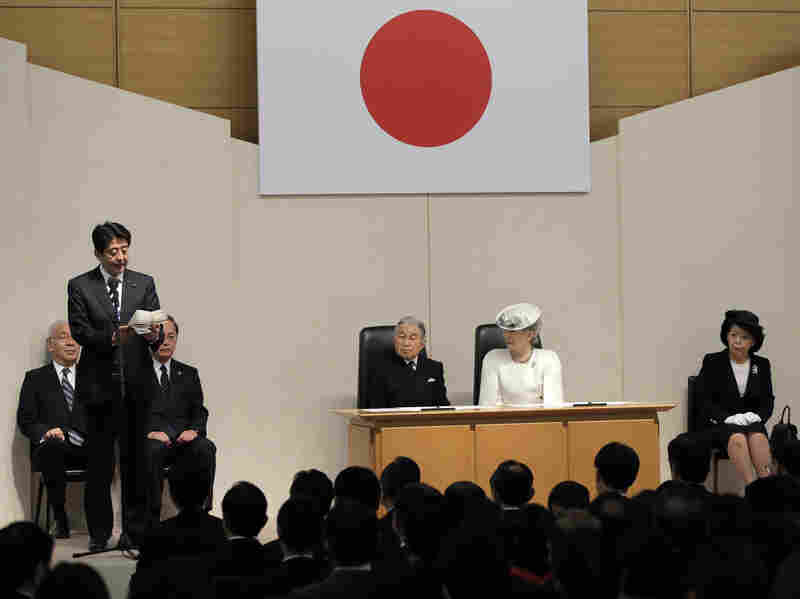 Japanese Prime Minister Shinzo Abe delivers a speech Sunday in Tokyo as Emperor Akihito, third from right, and Empress Michiko, second from right, listen during a ceremony marking the day Japan recovered its sovereignty under the San Francisco Peace treaty in 1952.