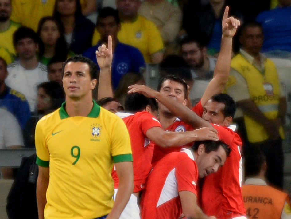 Chile's Marcos Gonzalez (center) celebrates with teammates after scoring against Brazil during their friendly football match on April 24. (AFP/Getty Images)